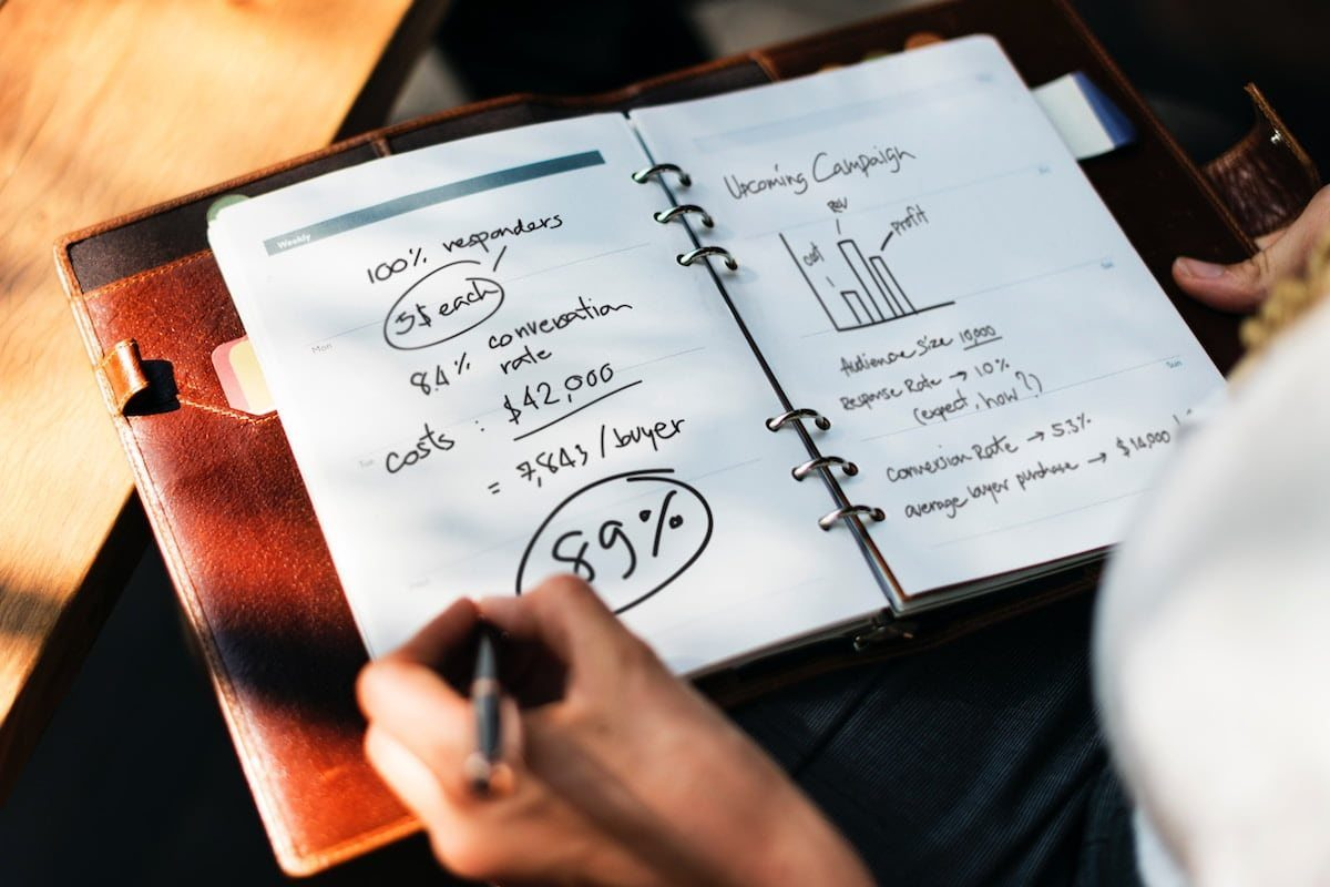 Una persona redactando un plan de campaña de marketing en un cuaderno en su regazo