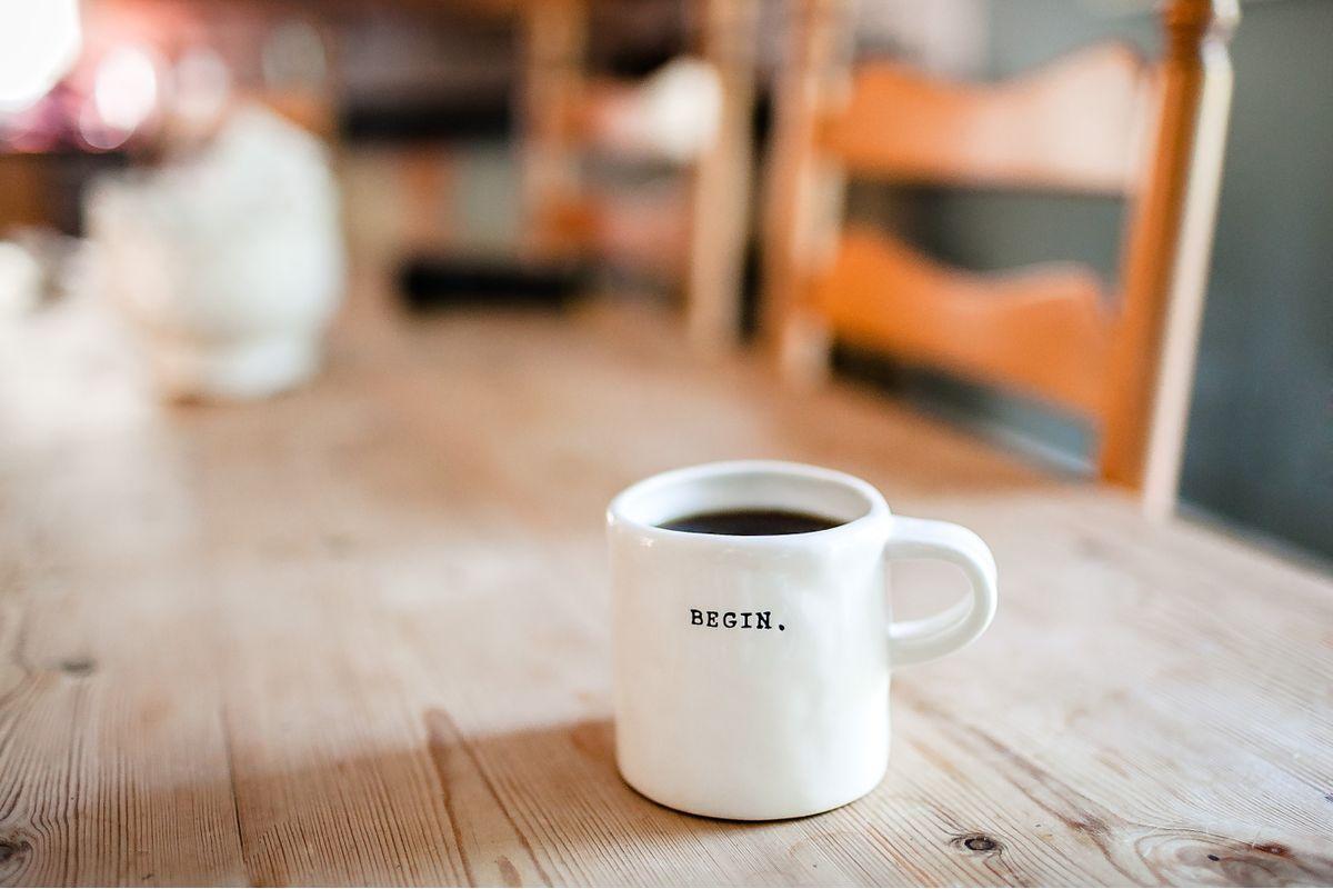 Taza de café con el texto «Begin» encima de una mesa