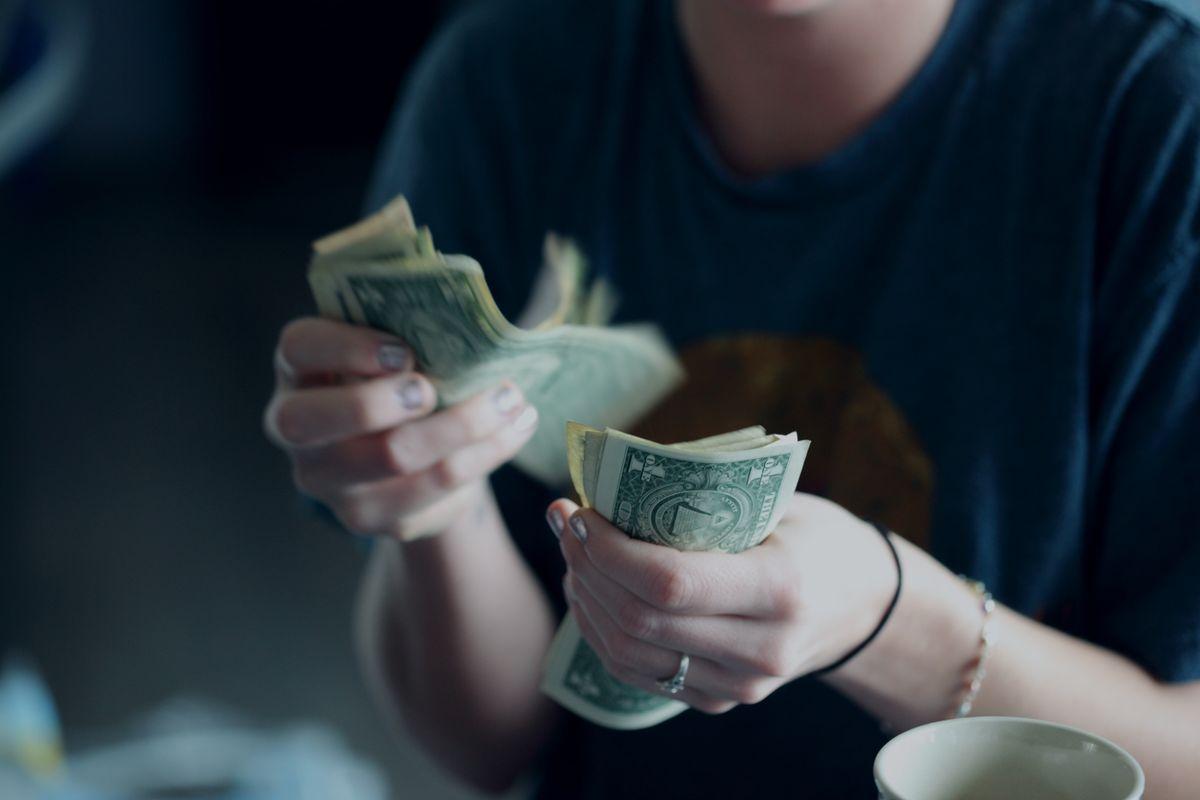 Young Woman Counting Money, de Sharon McCutcheon