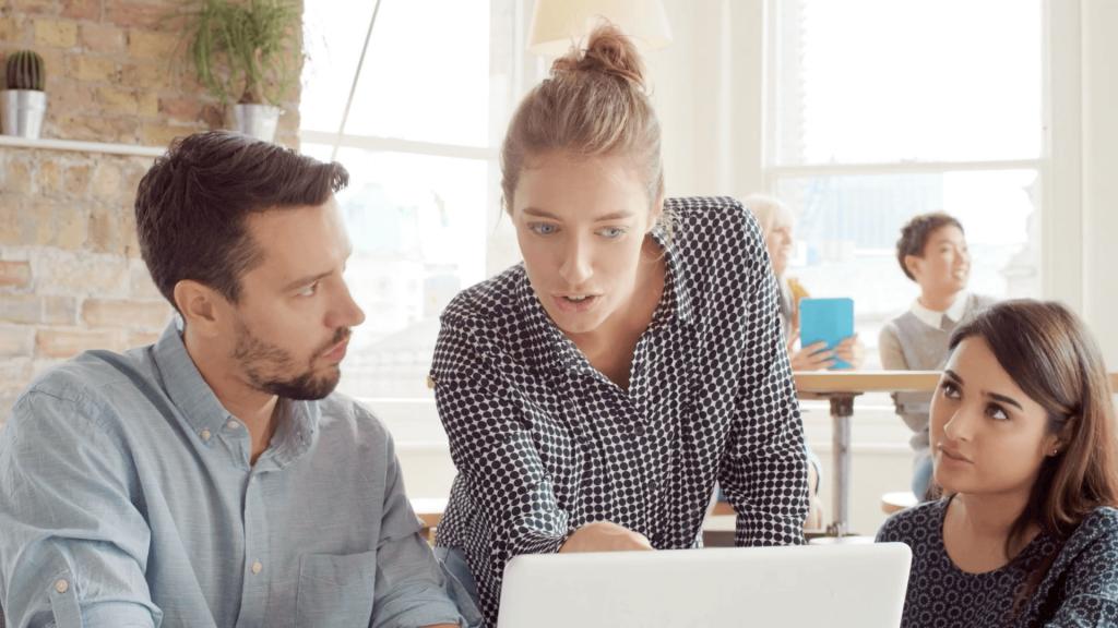 Imagen de stock con un hombre y dos mujeres comentando el contenido de su ordenador