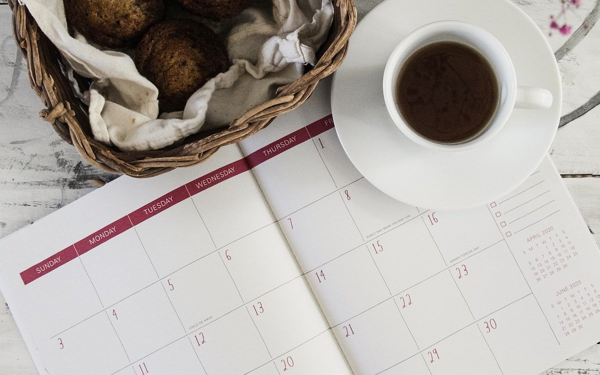 Foto de una agenda abierta y una taza de café encima