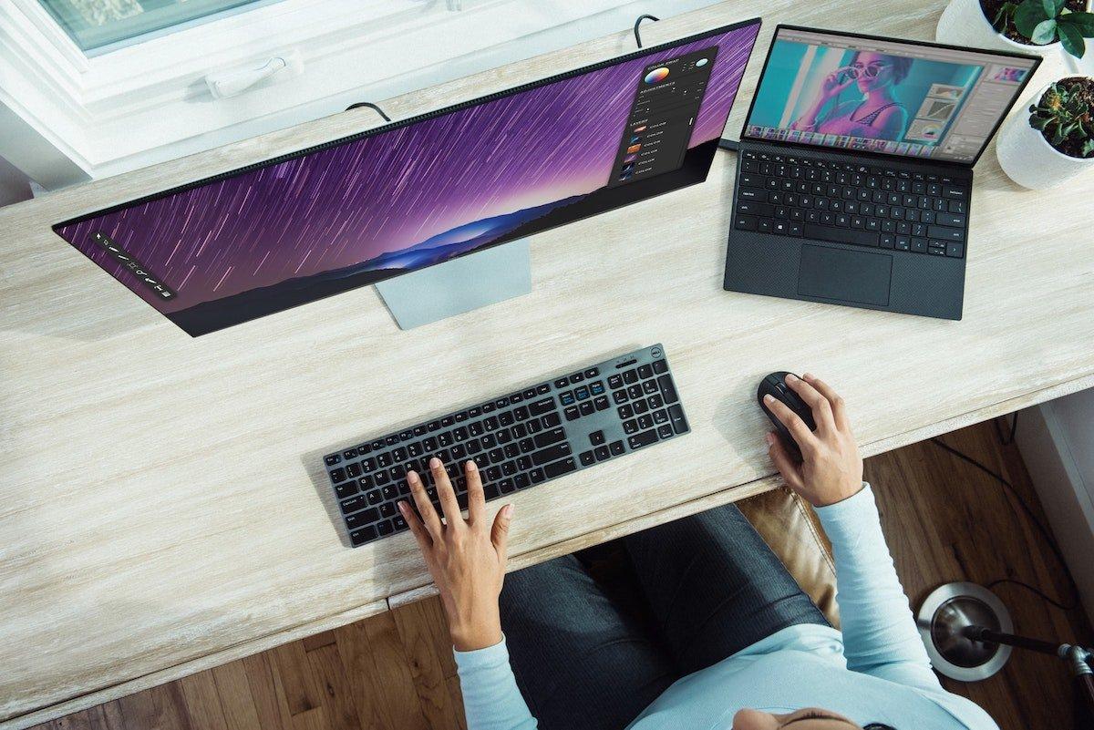 Foto aérea de alguien escribiendo en un portátil con una pantalla adicional