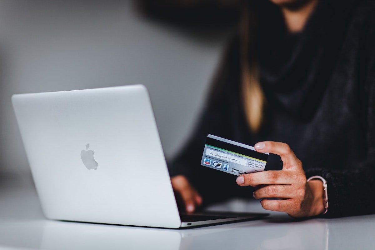 Foto de una persona realizando una compra online con una tarjeta de crédito