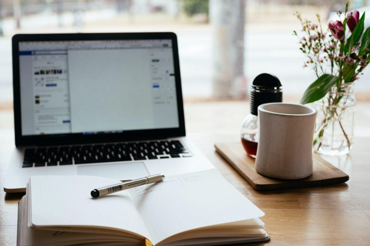 Foto de un escritorio con un portátil y una libreta