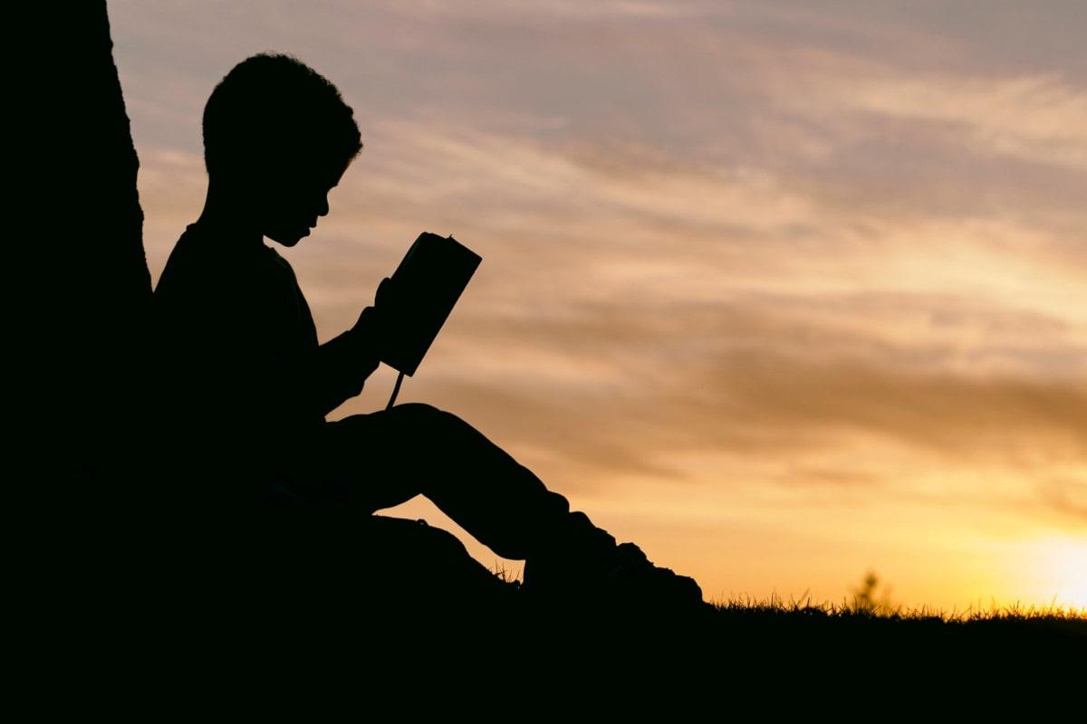 Silueta de un chico estudiando con una puesta de sol al fondo