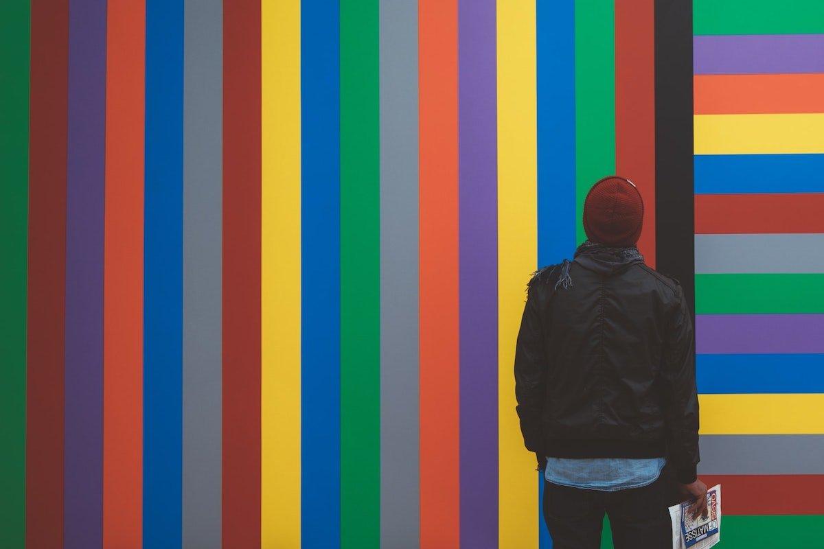 Foto de una persona mirando una pared pintada con líneas de colores