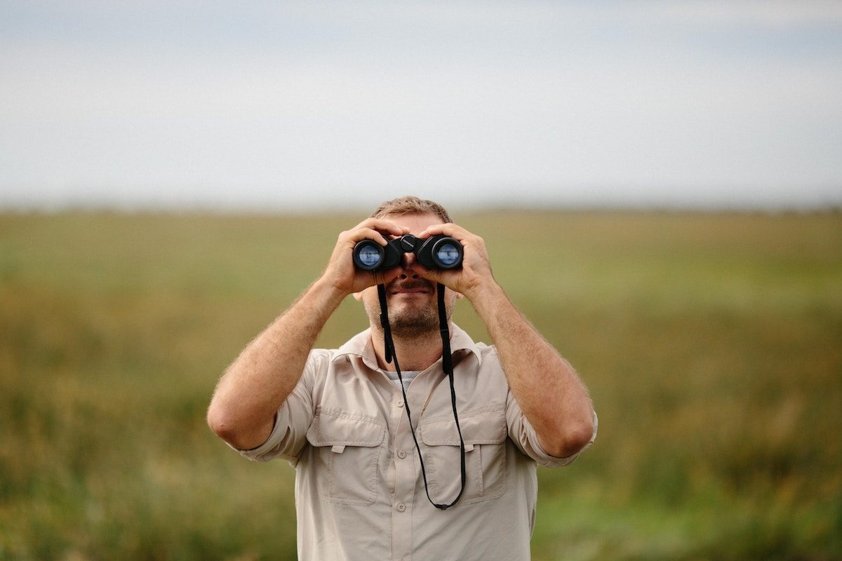 A man looking through his binoculars