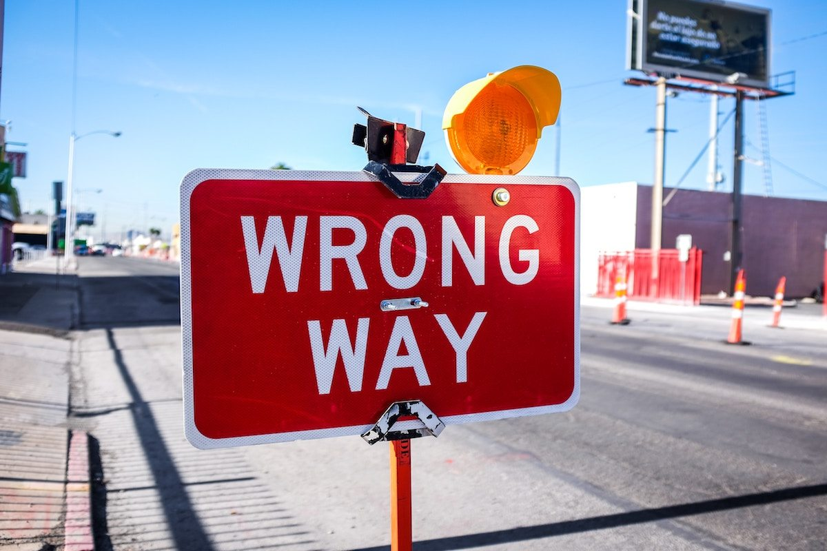 Red sign the wrong way down the road. Photo of NeONBRAND on Unsplash.