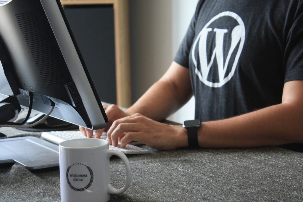 Guy working on a computer is wearing a WordPress shirt