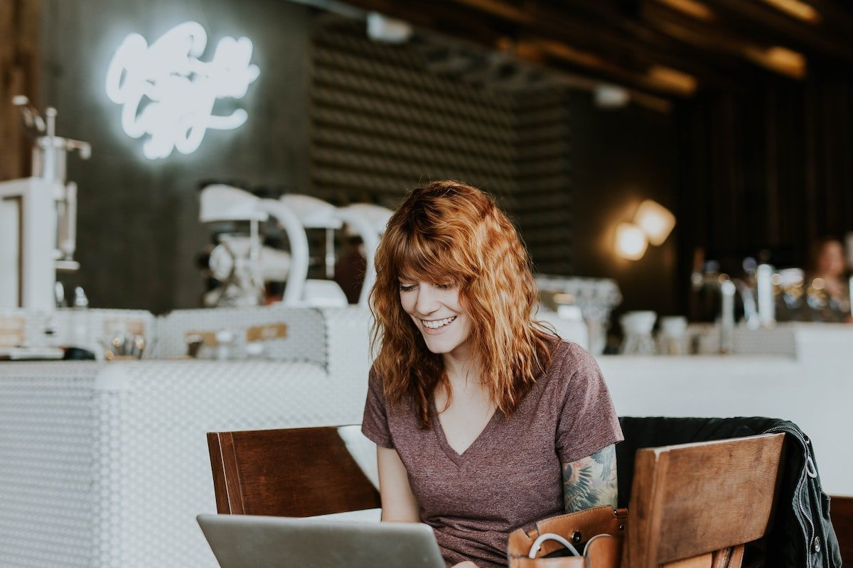 Photo of smiling woman looking at a laptop